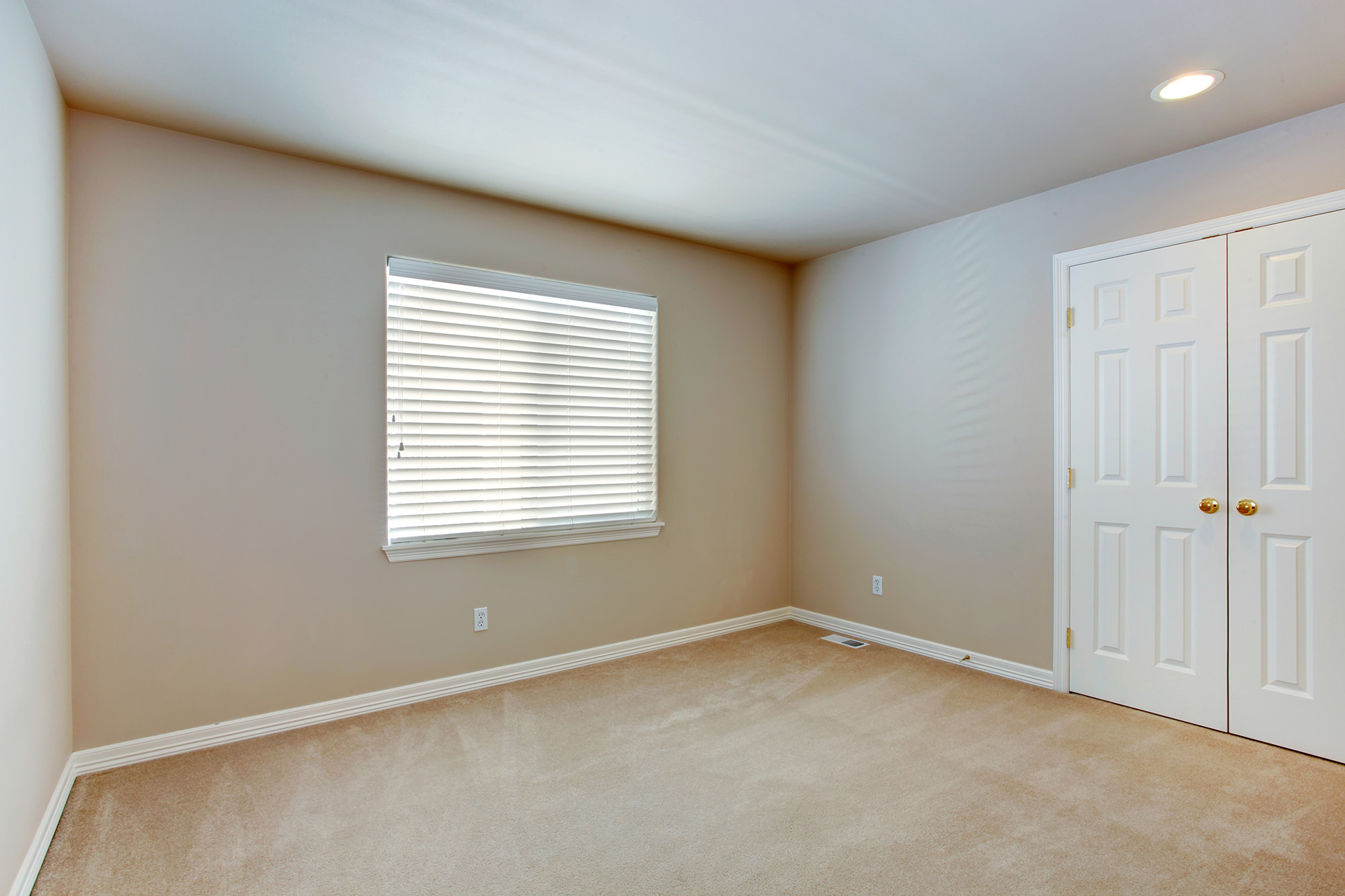 Simple empty room with light brown carpet floor